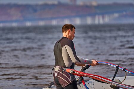 A male athlete is interested in windsurfing.
