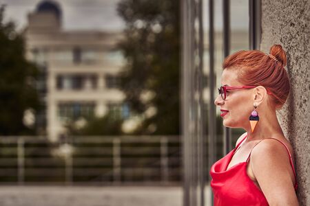 Portrait of a red-haired middle-aged woman in a red blouse standing against the wall. Cloudy summer day. Close-up. Фото со стока