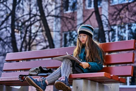 A teenager girl in glasses, a coat and a knitted hat sits on a bench in the park and draws a drawing on paper. Close-up. Sunny autumn day.