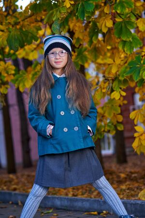 A teenager girl in glasses, a coat and a knitted hat on a walk in the autumn park.