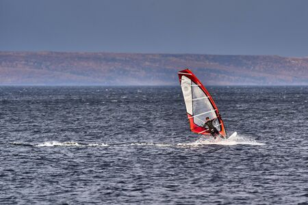 A male athlete is interested in windsurfing. He moves on a Sailboard on a large lake on an autumn day.