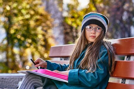 A teenager girl in glasses, a coat and a knitted hat sits on a bench in the park and draws a drawing on paper. Close-up. Sunny autumn day. Archivio Fotografico