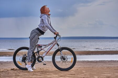 Red-haired middle-aged woman in sportswear on a bike walk on the sandy shore of a large river. Cloudy summer day.