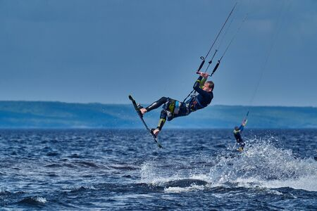 A male kiter slides on the surface of the water. Splashes of water fly apart.