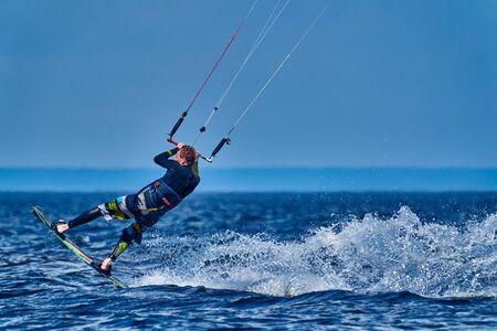 Un kiter mâle glisse à la surface de l'eau. Des éclaboussures d'eau s'écartent. Fermer. Banque d'images