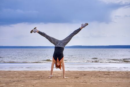 A middle-aged woman with red hair does gymnastics on the sandy shore of a large river. Cloudy spring morning.