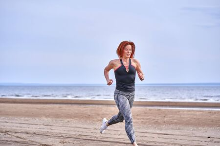 A red-haired middle-aged woman in sportswear runs along the sandy shore of a large river on a cloudy summer morning. Healthy lifestyle.