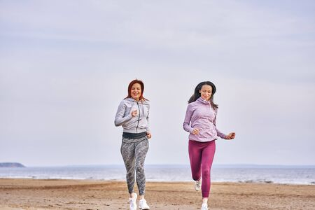 Two women are jogging along the sandy bank of a large river. Women do gymnastics in the summer morning. 스톡 콘텐츠
