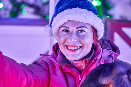 Portrait of a smiling middle-aged woman for a walk on Christmas night.
