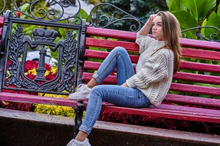 Portrait of a young woman with long blond hair and in a white knitted sweater, blue jeans and white sneakers sitting on a park bench in the autumn evening. 스톡 콘텐츠