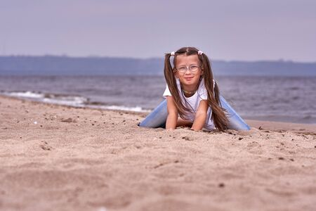 Portrait of a teenage girl in glasses and a white T-shirt walking on a sandy shore on a cloudy autumn day.