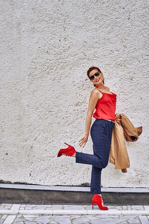 Portrait of a red-haired middle-aged woman in a red blouse  and in sunglasses  standing against the wall. Cloudy summer day. Close-up.