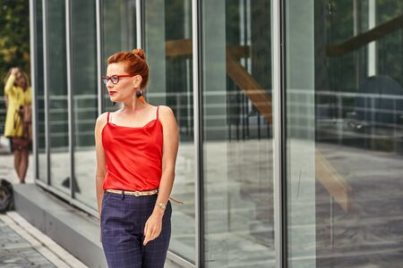 Portrait of a red-haired laughing middle-aged woman in a red blouse standing against the wall. Cloudy summer day. Close-up. 스톡 콘텐츠