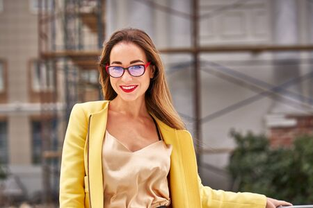 Portrait of a young beautiful laughing woman with long hair wearing glasses and a yellow jacket on a windy cloudy day.