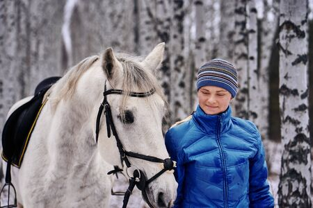 Young pretty woman in a blue jacket and a sports hat for a walk with a white horse in the winter birch forest.