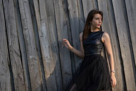 Portrait of a young slim woman brunette in a black dress near a wooden fence. Summer sunny evening. Close-up.
