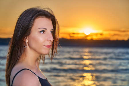 Portrait of a young brunette girl against the backdrop of the sunset over a large lake. Close-up of the girl's face.