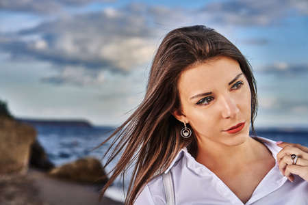 Portrait of a young brunette girl against the background of the evening sky over the sea. Close-up of the girl's face.