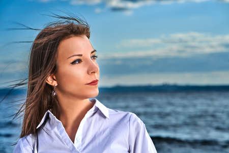 Portrait of a young brunette girl against the background of the evening sky over the sea. Closeup of the girl's face.