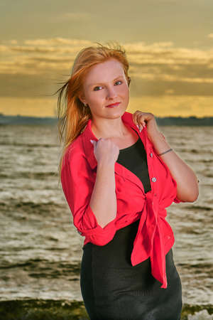 Portrait of a young red-haired girl on an evening walk along the seashore. Summer sunny evening. Stok Fotoğraf