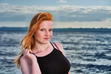 Portrait of a red-haired girl standing by the sea. Stok Fotoğraf