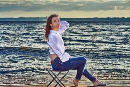 A young brunette woman in a white blouse and blue jeans sits and rests on the sandy seashore. Sunny summer evening.