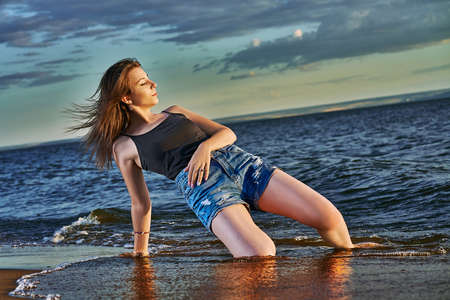 A young brunette woman in a black undershirt and denim shorts resting on the sandy seashore. Summer sunny evening. Stok Fotoğraf