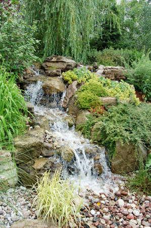 пышной листвой: Искусственный водопад функция в окружении пышной листвы в сад Фото со стока