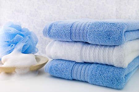 bath: Three fold bath towels, bar of soap and a blue shower sponge. Stock Photo