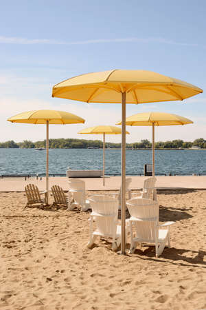 toronto: HTO is a public urban beach in Toronto. The parks standout feature is a sandpit that holds Muskoka chairs and enormous fixed yellow metal umbrellas. Stock Photo