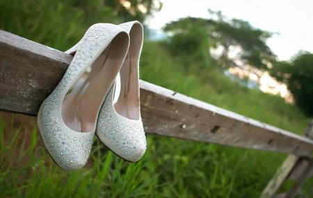 chaussures de mariage mariée accrochés à la clôture en bois au champ d'herbe