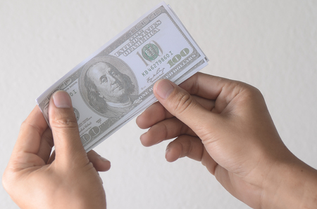 A mans hand holding America Dollar Note or money background, business concept