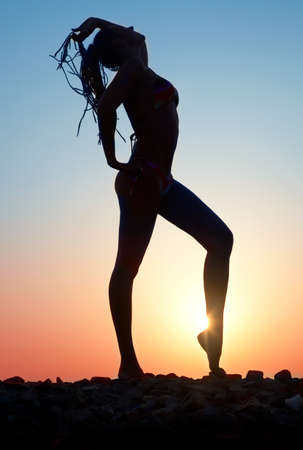 Beautiful female figure against the evening sun photo