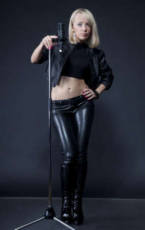 beautiful blonde with a microphone on black isolated background Stock Photo