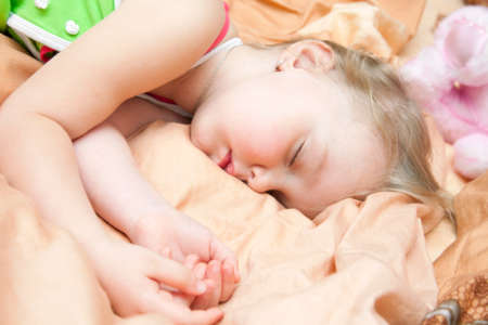 A little girl sleeps in a crib