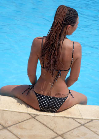 A woman sits on the edge of the swimming pool with turquoise water photo