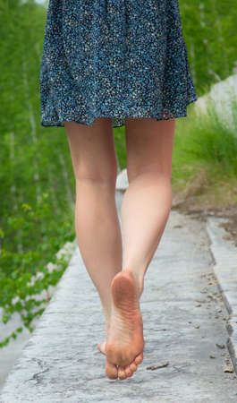 piedi nudi di bambine: Una giovane donna va a piedi nudi sul parapetto di pietra Archivio Fotografico