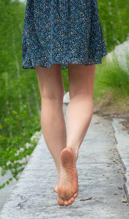 descalza: Una joven va descalzo sobre el parapeto de piedra Foto de archivo