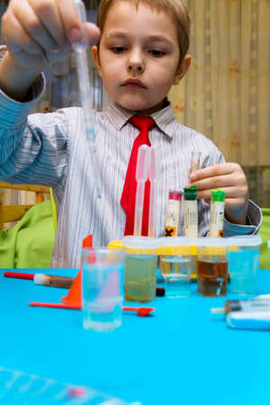 The boy enthusiastically studying chemistry and makes his first experience in chemical Stock Photo