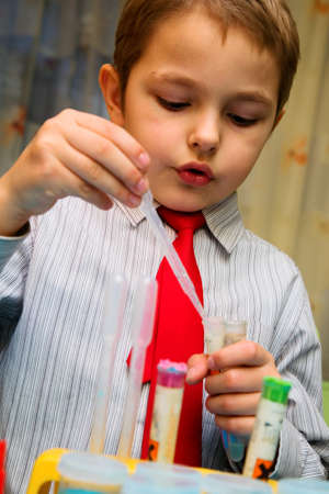 The boy enthusiastically studying chemistry and makes his first experience in chemical Stock Photo - 12202220