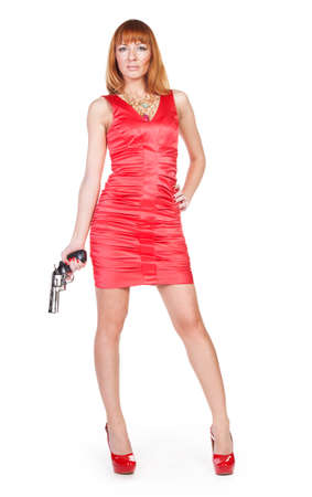 Beautiful woman in a red dress with a gun in his hand on a white background photo