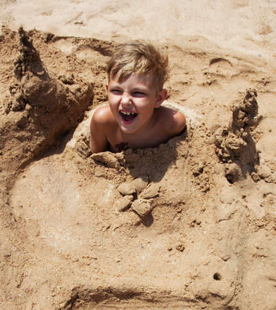 boy on the beach buried in sand on a summer day photo