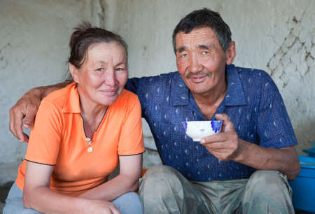 A man and a woman of Asian appearance have tea at home photo