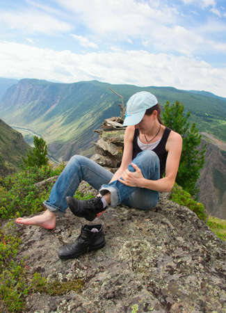A young woman takes off on a halt hiking boots in the tracking photo