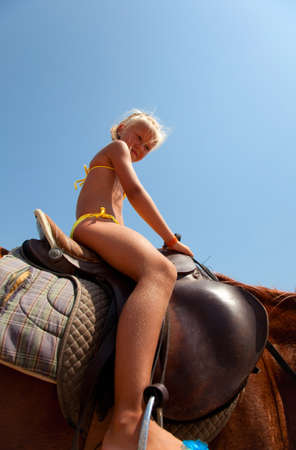 age 5: Children riding on horseback on the beach Stock Photo