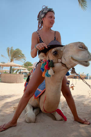east riding: Young beautiful woman with a camel on the beach in Egypt
