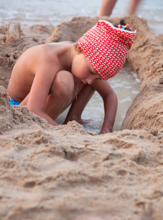 Cute little girl busy building sand castles on the beach photo