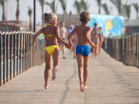 Boy and girl go on the pier taking each other
