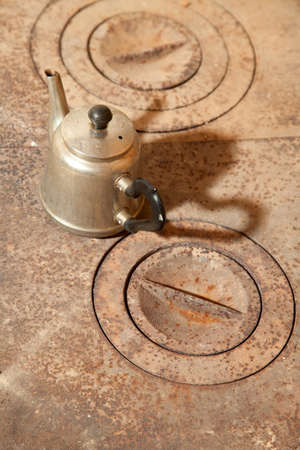 Kettle on a rusty old cast iron stove Stock Photo - 12412960