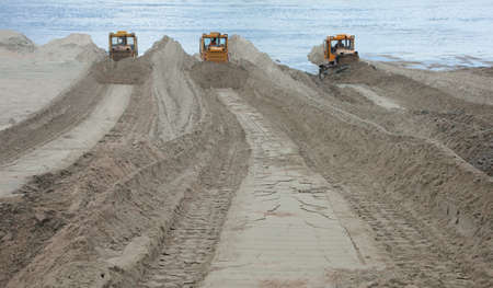 sand quarry: Bulldozer on the banks of the river moves the sand Stock Photo